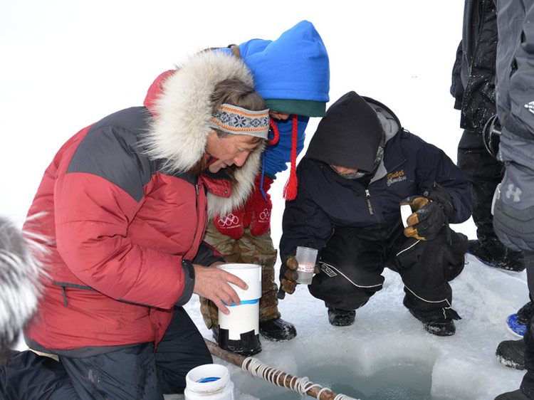 Marine science professor Ken Dunton takes water samples with high school students from Kaktovik, Alaska. Through the Student Sampling Program, students interns are paid to collect samples throughout the year. Their dataset will be the first of its kind.
